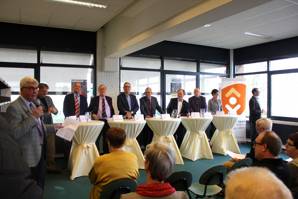 Kandidaten klaar voor debat, met uiterst rechts een afgedwaalde Van Hulle